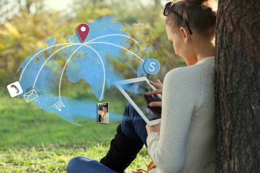 Concept of sitting young woman using her tablet pc during rest in the park